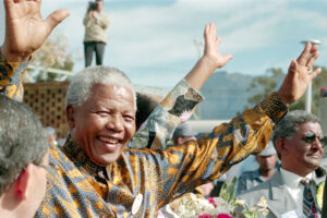 Nobel Laureate and former President of South Africa from 1994 to 1999 Nelson Mandela waves at his audience.